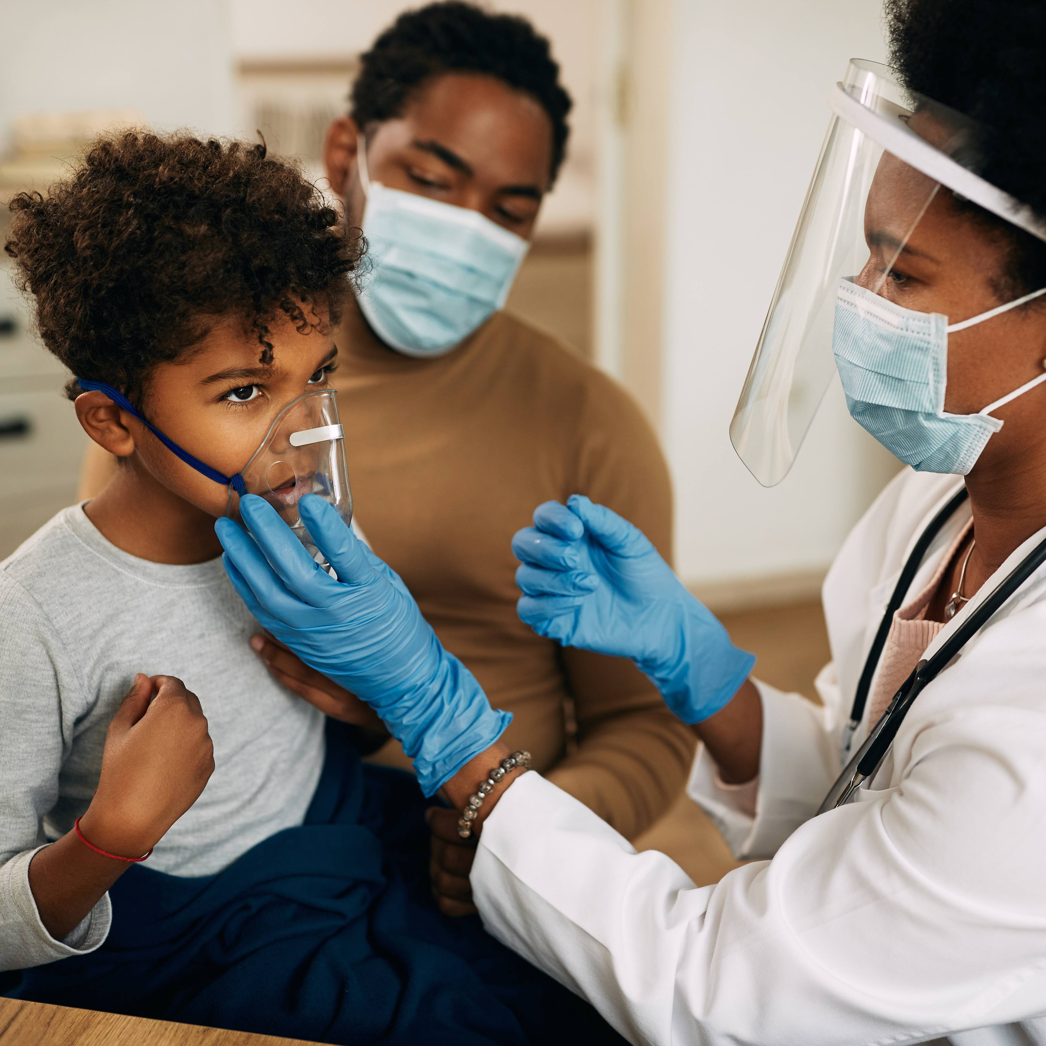 a young Black boy with asthma in a doctor's exam room with his mom and the physician helping him breathe, all wearing masks