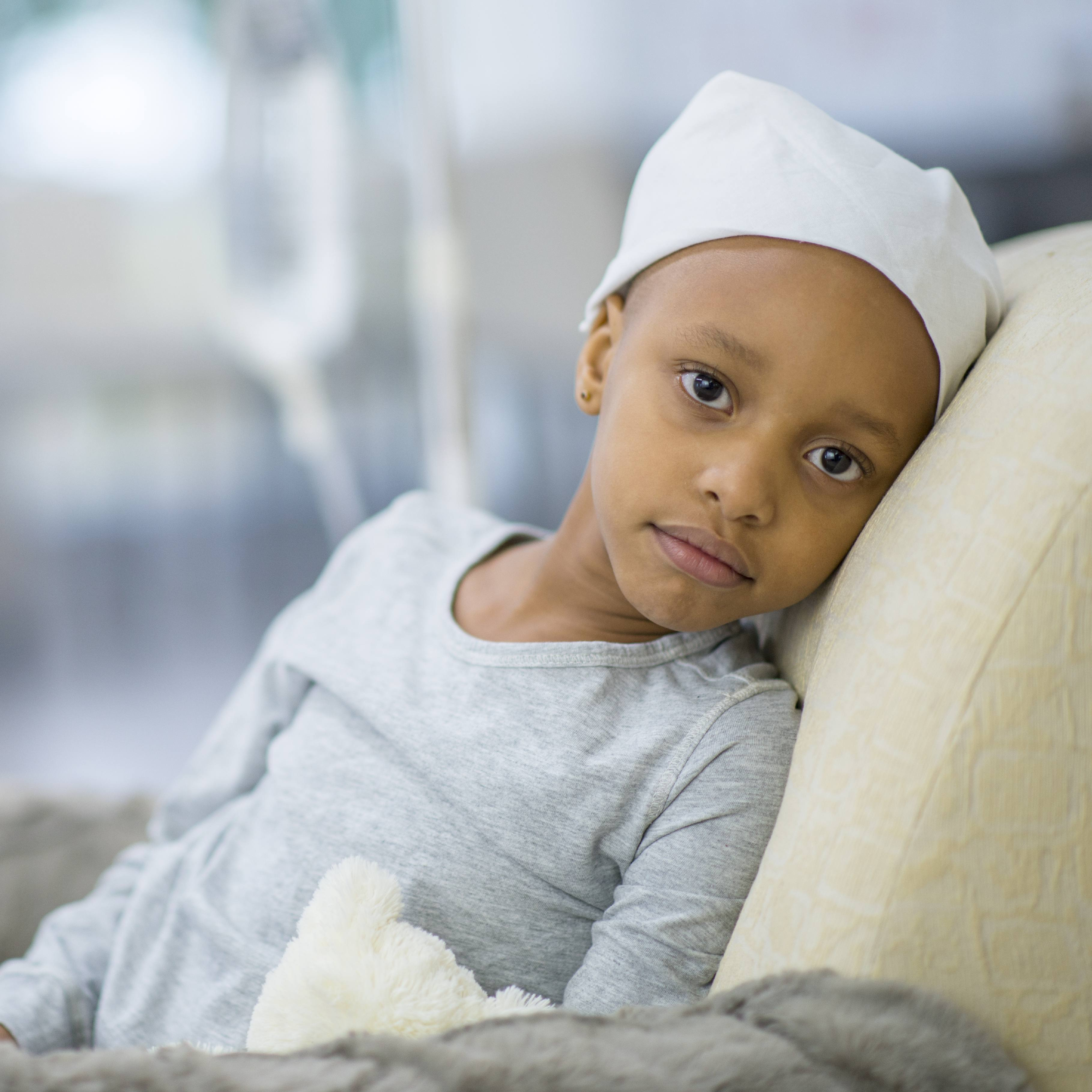 a young Black, maybe Asian, child in the hospital with an IV, perhaps sick with cancer