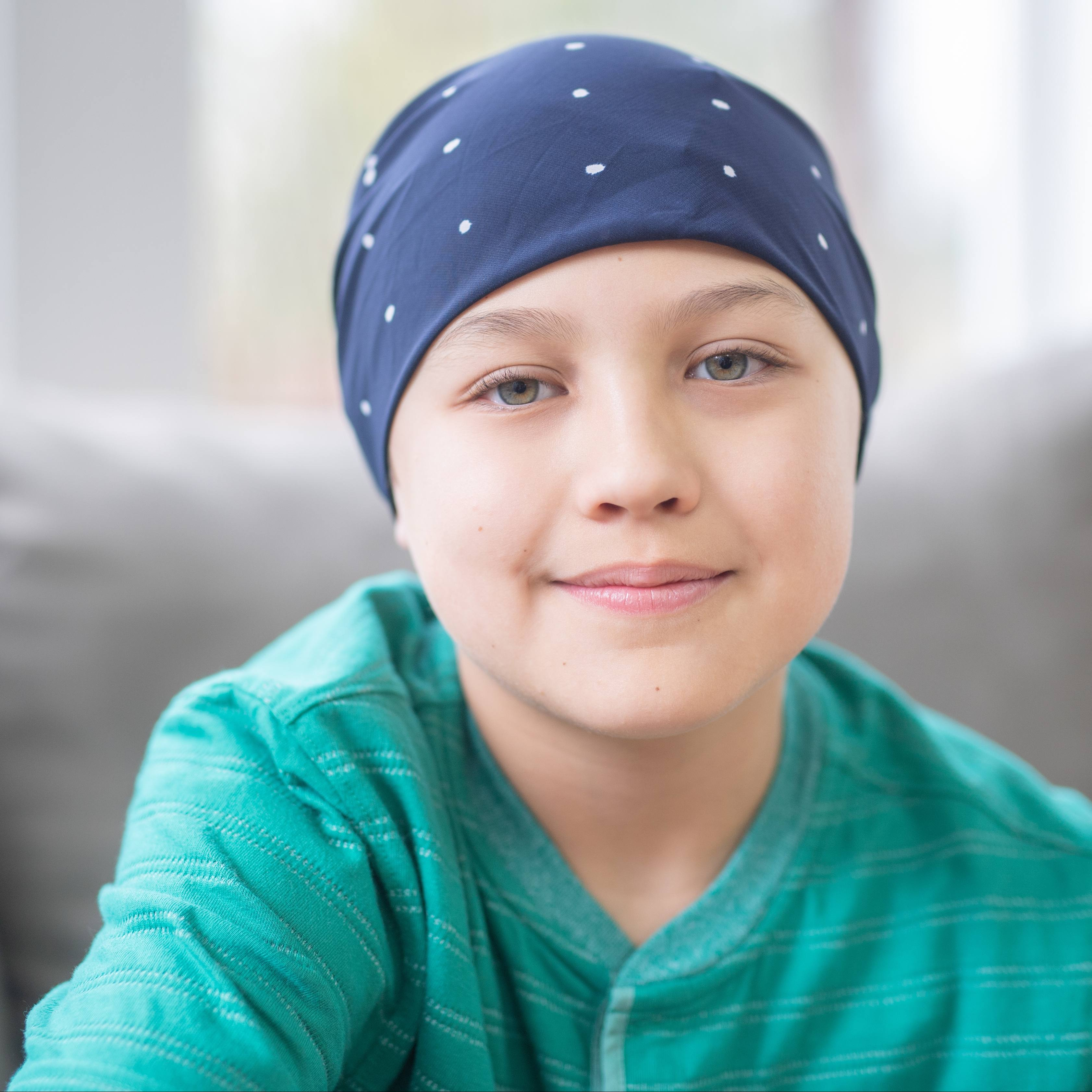 a young white child softly smiling, wearing a scarf wrap as if they have cancer and are receiving chemo therapy