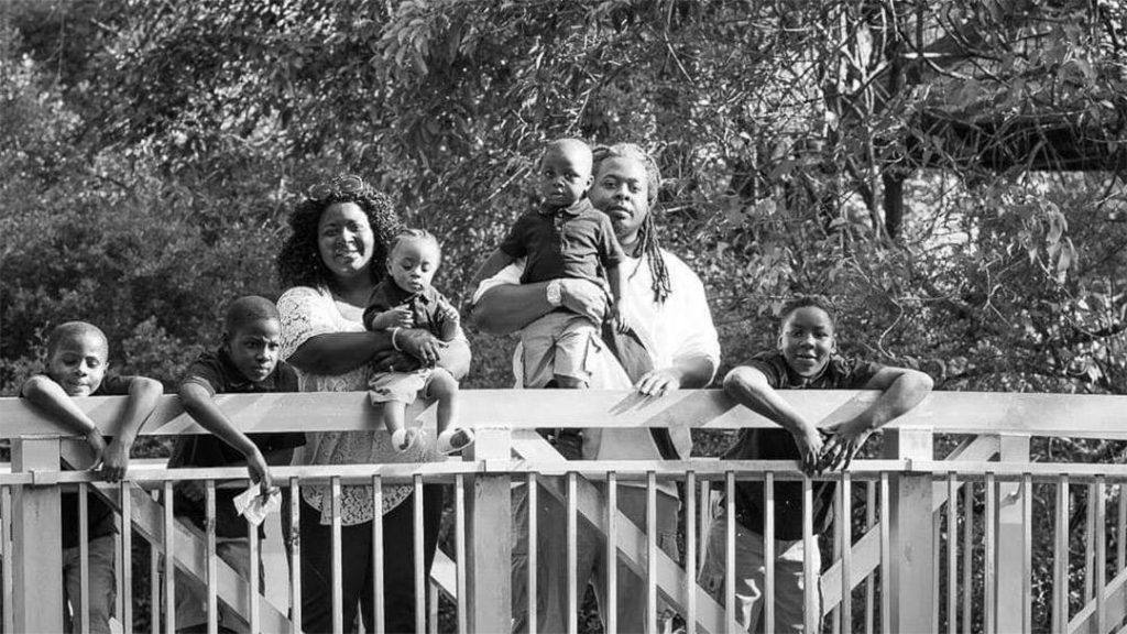 black and white photo of cancer patient Felicia Curtis with her family standing outside on a bridge