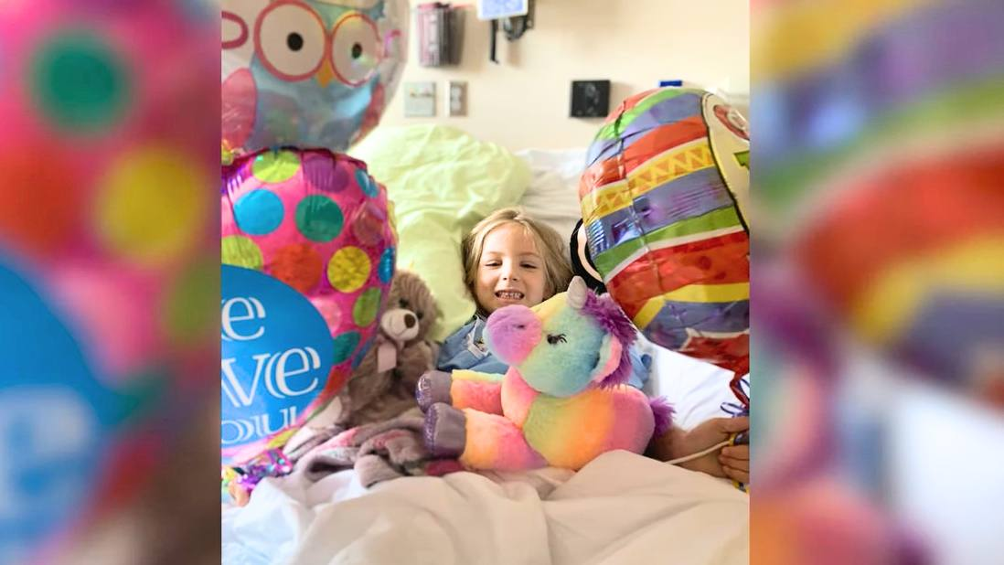 cancer patient Kenedi in hospital bed with stuffed animals