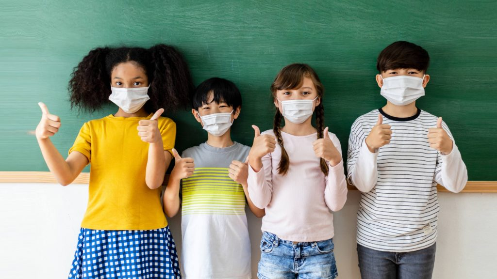 four school aged children wearing masks and standing near chalkboard with their thumbs up