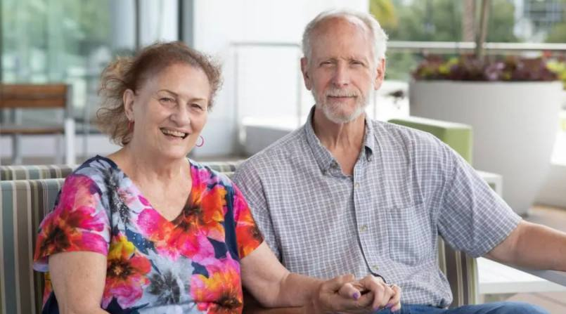 multiple myeloma patient Ann Arneson smiling and sitting on the couch with her husband