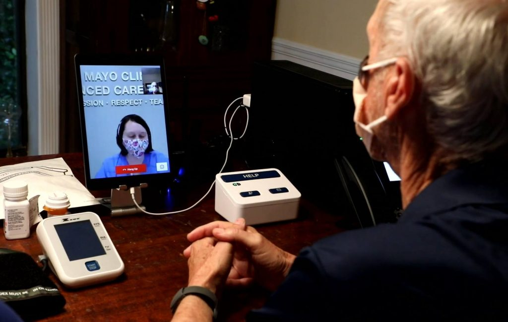 patient John Jolly on a video call with a nurse while in his home