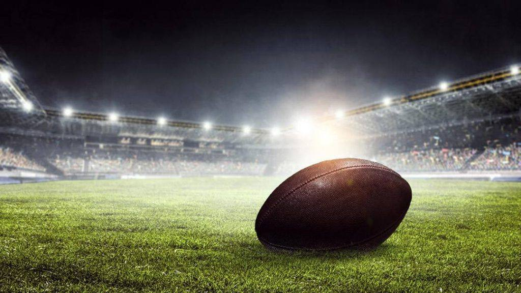 Football on a field in a stadium at night with lights