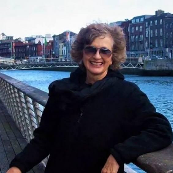 Florida patient Joy Carol smiling outside near a river