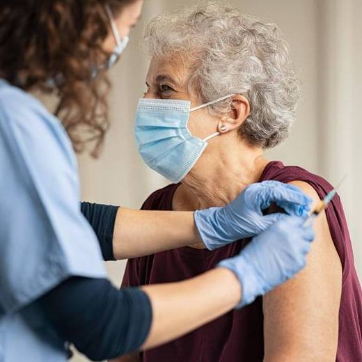 older white woman wearing a face mask and having her COVID-19 vaccine