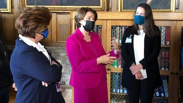 Sen. Amy Klobuchar wearing bright pink for Breast Cancer Awareness talking with Mayo leaders in Plummer Library