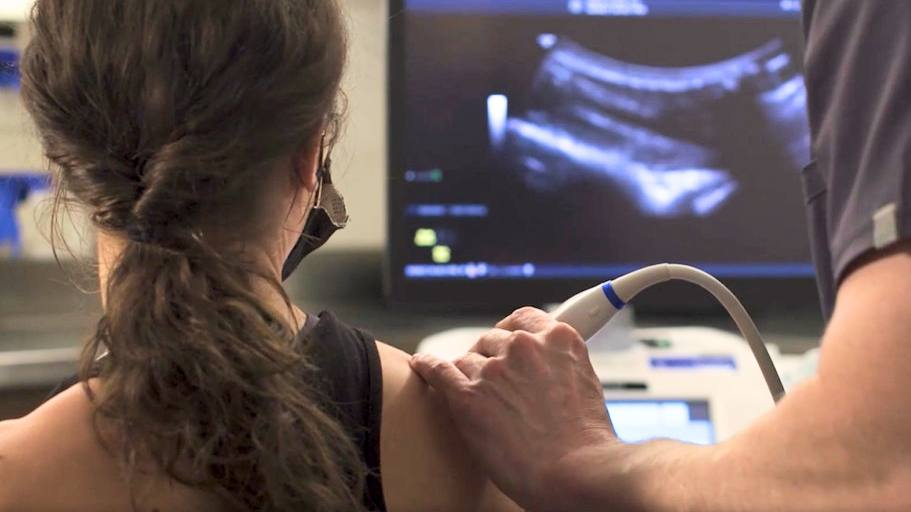 Young white woman athlete having shoulder injury ultra sound with sports medicine expert