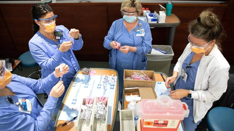 a group of Mayo Clinic staff, women, standing around a table wearing masks, goggles and working with COVID-19 vaccines