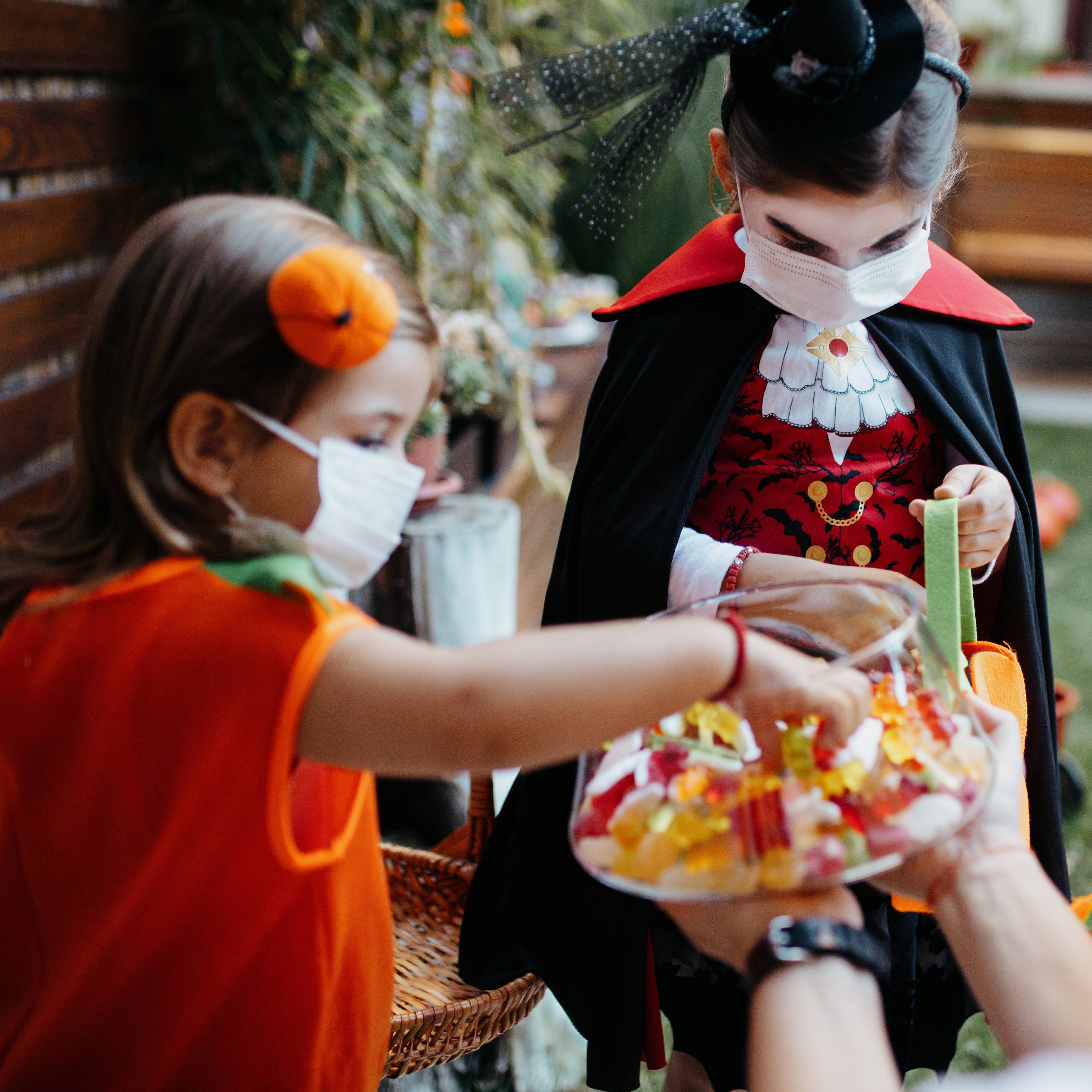 a group of young children in Halloween costumes, trick or treating, wearing face masks, COVID-19