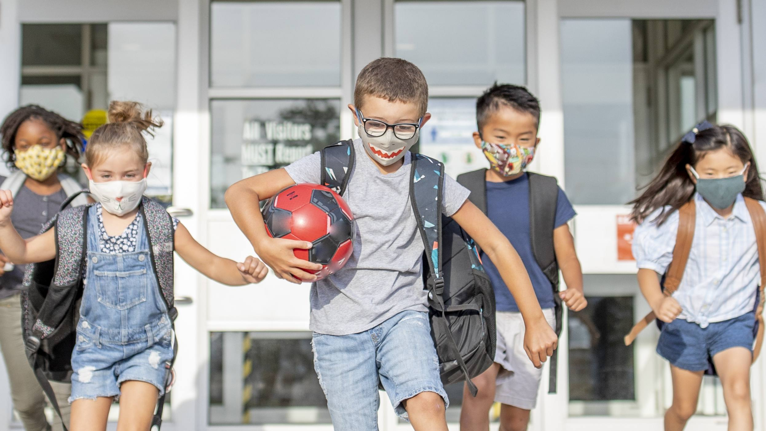 a group of young, diverse elementary school children wearing masks and running outisde