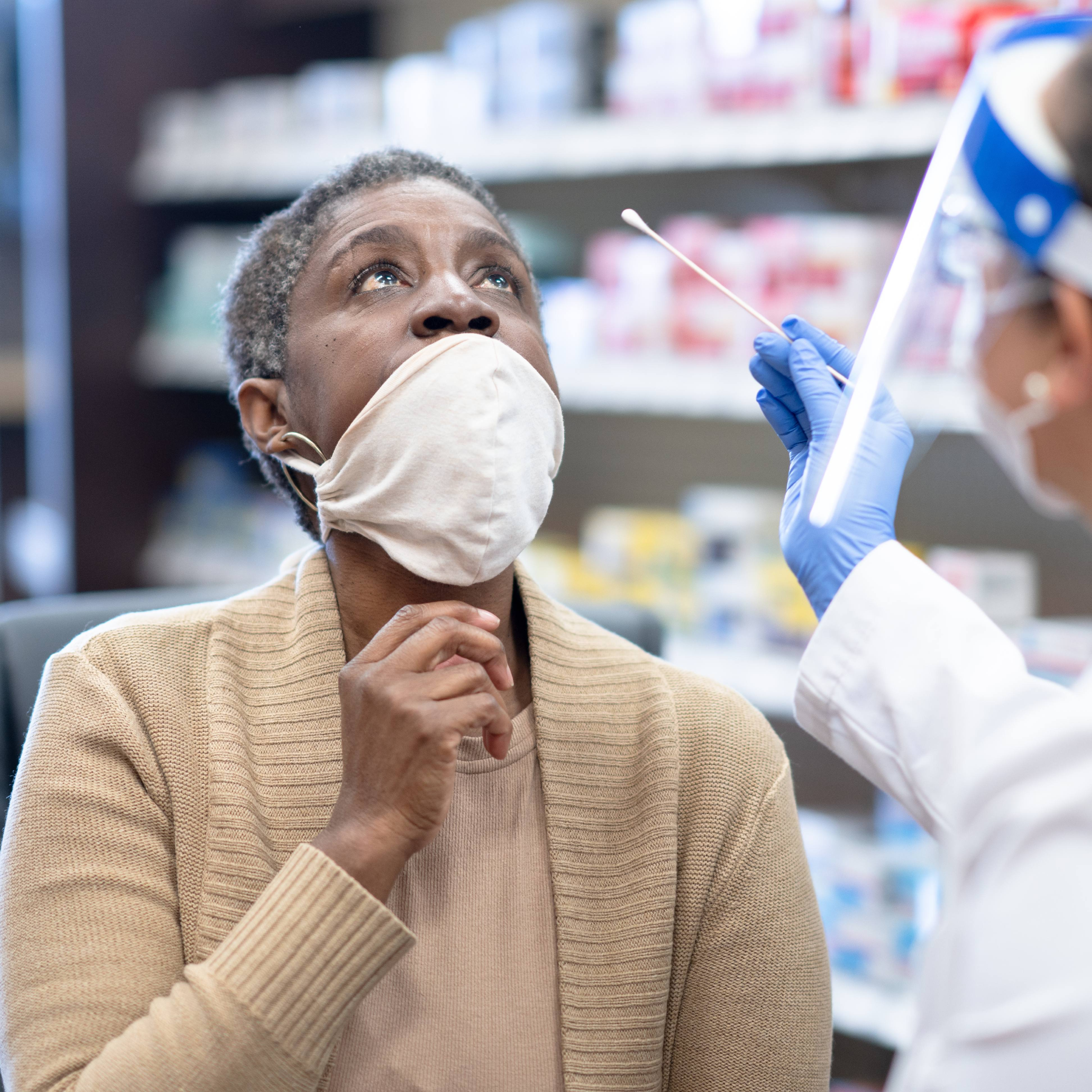 a middle-aged Black woman pulling down her mask to be swabbed and tested for COVID-19 by a pharmacist wearing PPE