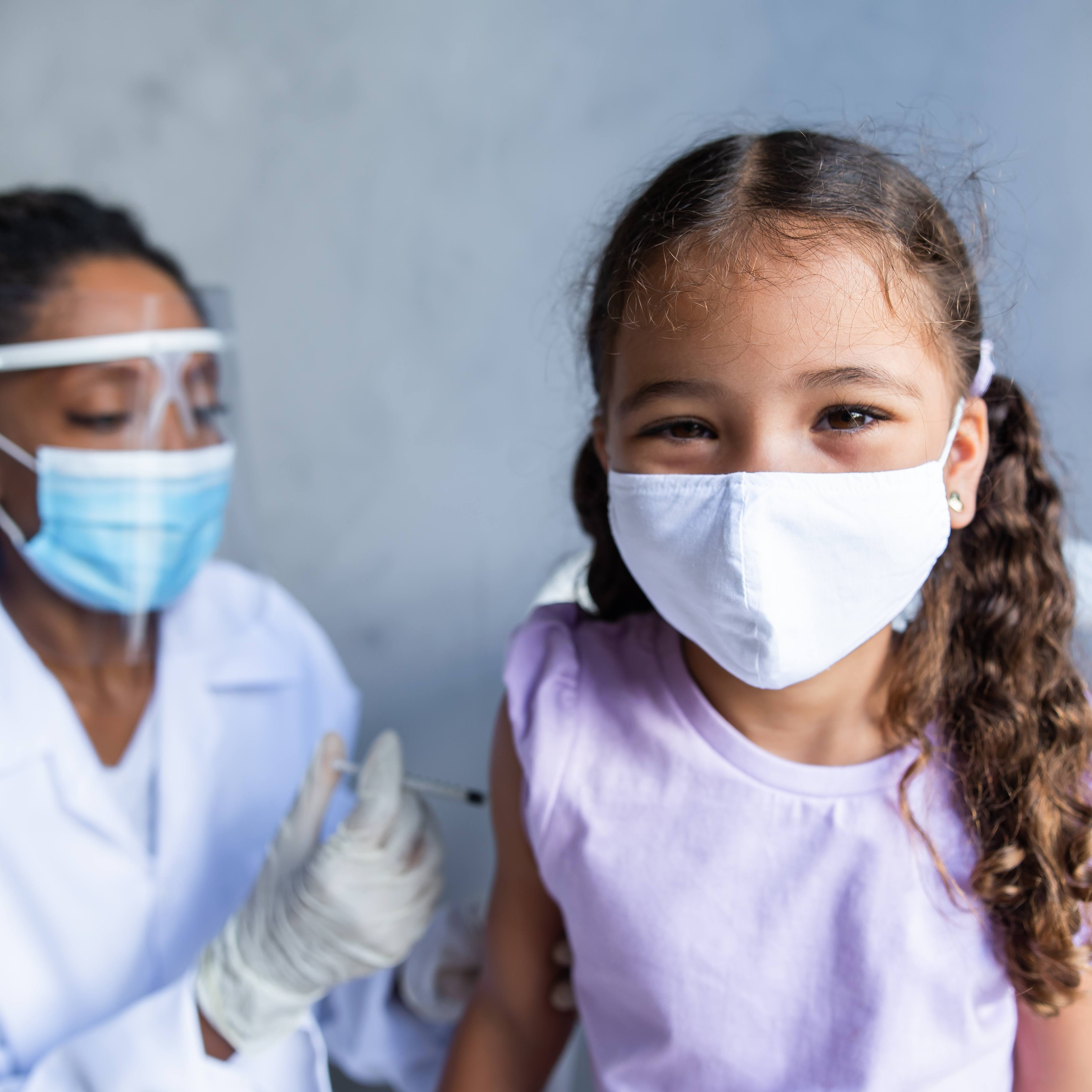 an elementary school aged Latina or Black girl wearing a mask getting a vaccination