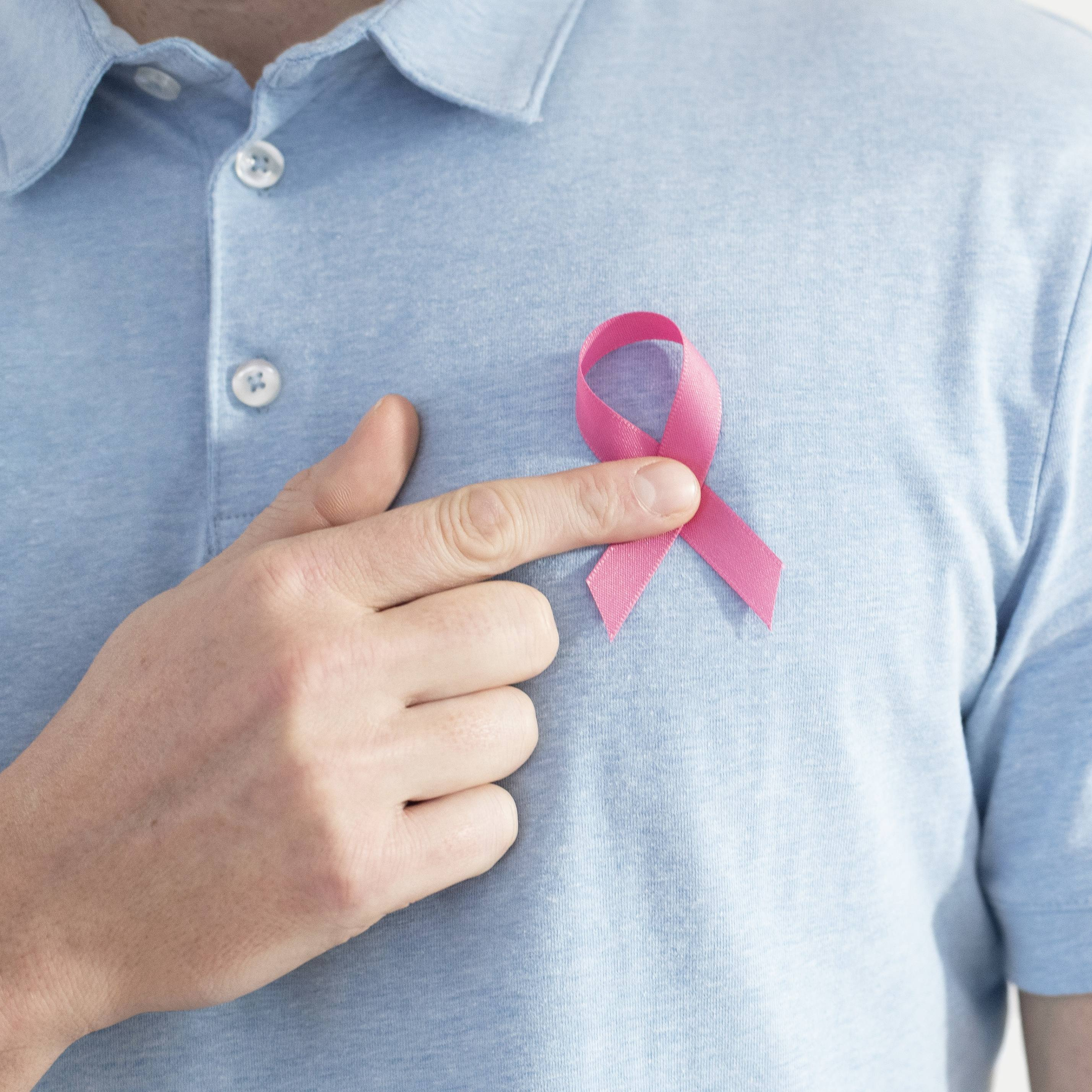 closeup of a white male pointing to a pink breast cancer ribbon on his chest