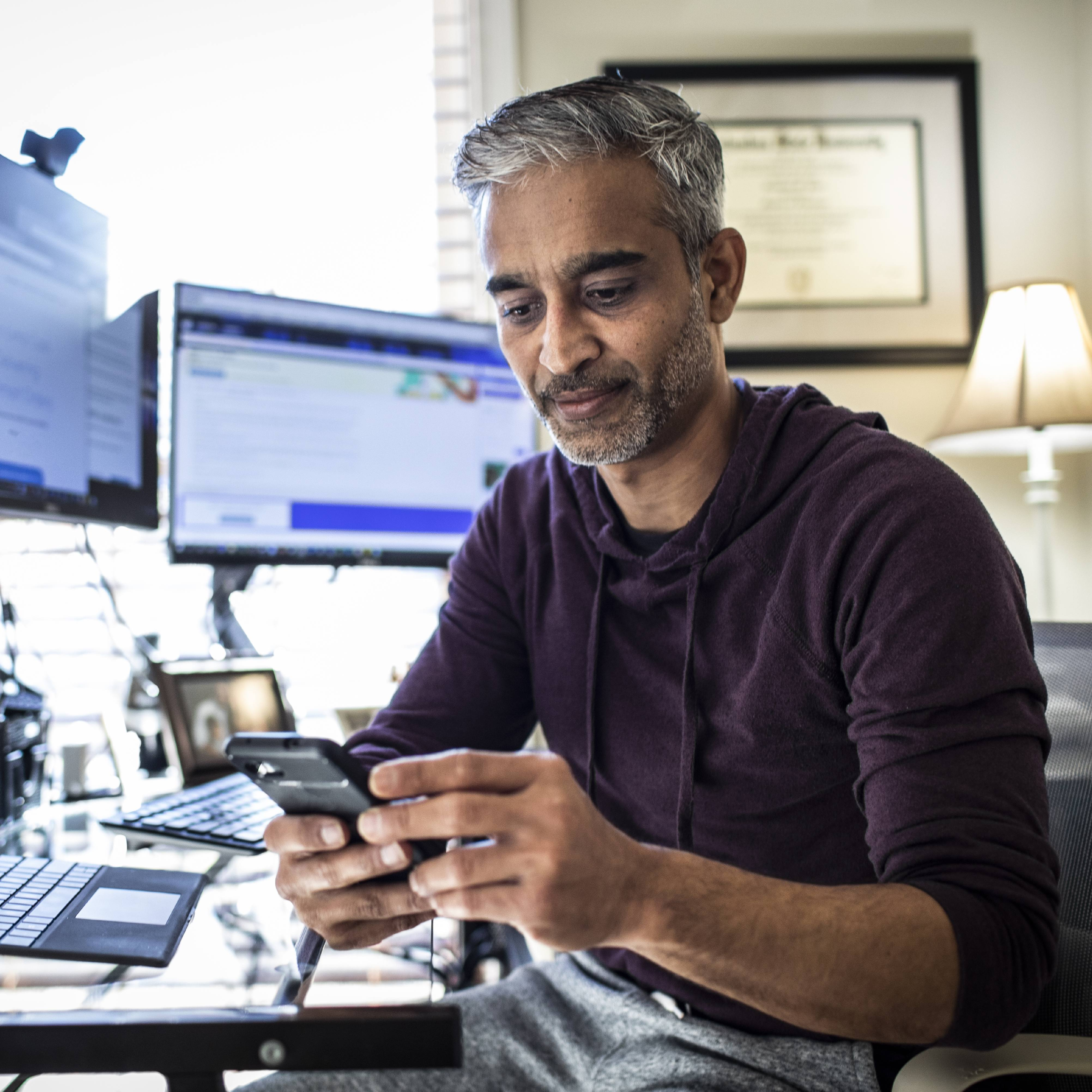 middle aged man, perhaps Middle Eastern, sitting at a home office desk with computer monitors