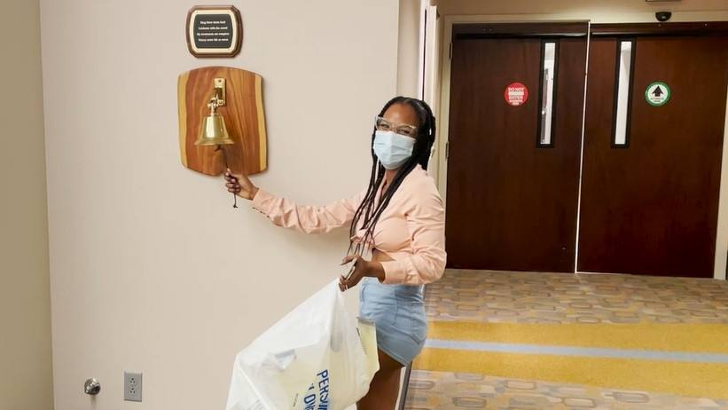 young Black woman, breast cancer patient Jessica Florence, wearing mask and ringing the bell