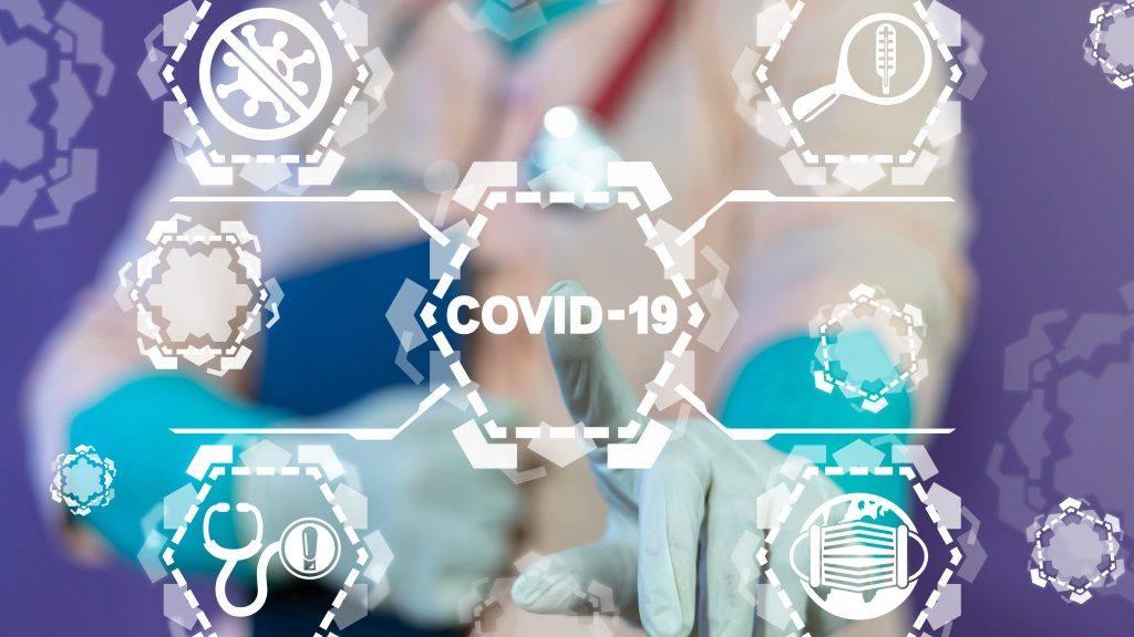 一个带有医疗图标的文字图形,中间写着COVID-19,还有一只戴着医用手套的手指向这个词